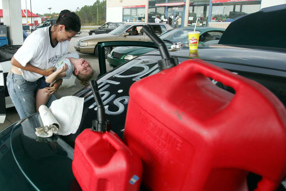 Nicole Ward kills time by playing with her daughter Breannan, 7, while waiting in line for gas in Moss Point, Miss. Ward had been waiting in line for over three hours, waiting for the station to get a generator in to start the pumps. Photo: ROB CARR, AP / AP