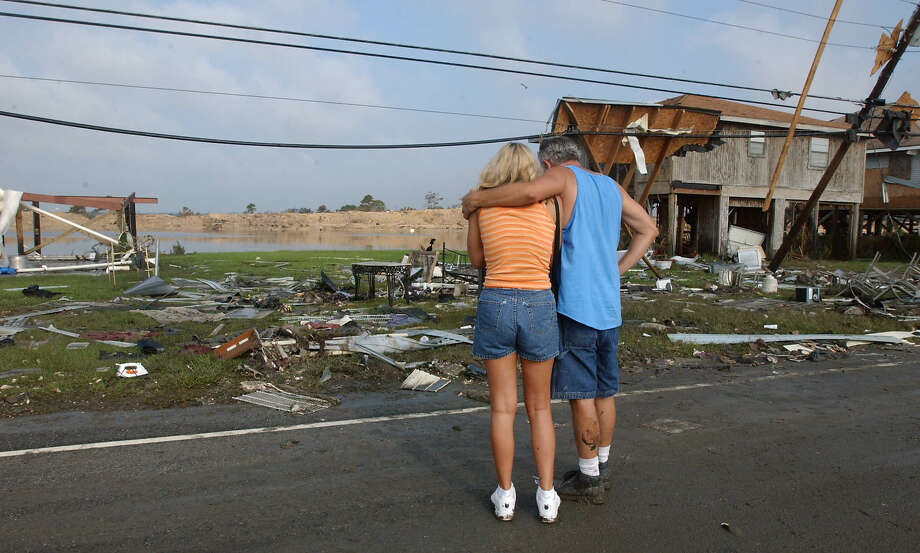 Gerry and Joe Catanese embrace as they get a first look at what once was their home, far left, in the wake of Hurricane Katrina in the Pirate's Harbor subdivision in Slidell, La. Photo: MARI DARR-WELCH, AP / AP