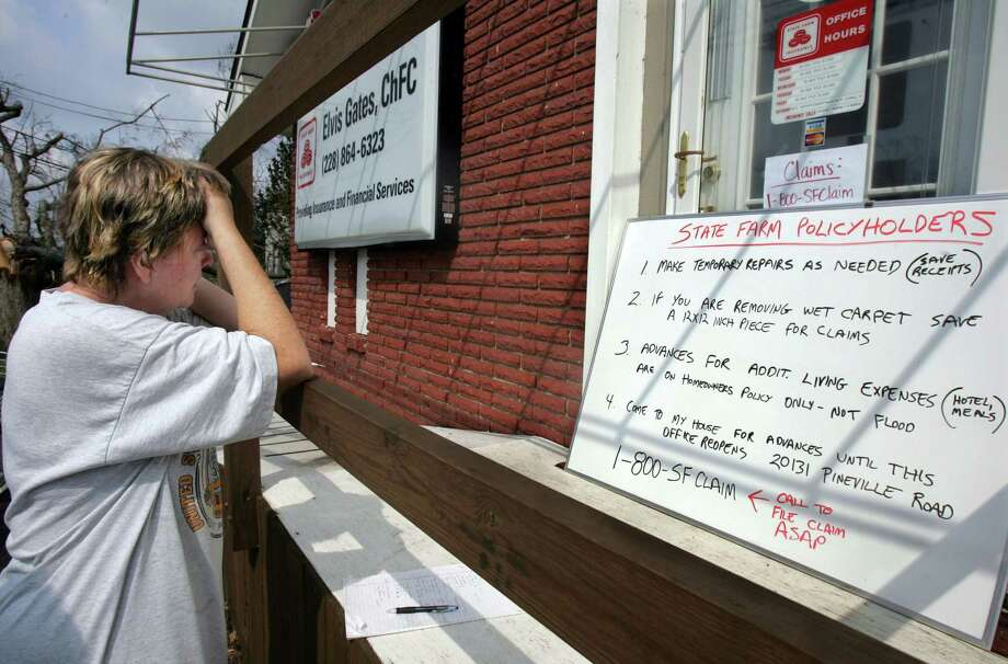Cindy Brickman reads instructions on how to file an insurance claim outside an insurance office in Long Beach, Miss. Photo: M. SPENCER GREEN, AP / AP