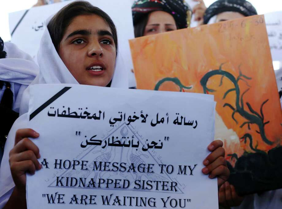 An Iraqi Yazidi woman holds a placards during a protest outside the United Nations (UN) office in the Iraqi city of Arbil, the capital of the autonomous Kurdish region, on August 2, 2015 in support of women from their community who were kidnapped last year in the Sinjar region by the Islamic State (IS) group jihadists. In 2014, the jihadists massacred Yazidis, forced tens of thousands of them to flee, captured thousands of girls and women as spoils of war and used them as sex slaves. AFP PHOTO / SAFIN HAMEDSAFIN HAMED/AFP/Getty Images Photo: SAFIN HAMED / AFP