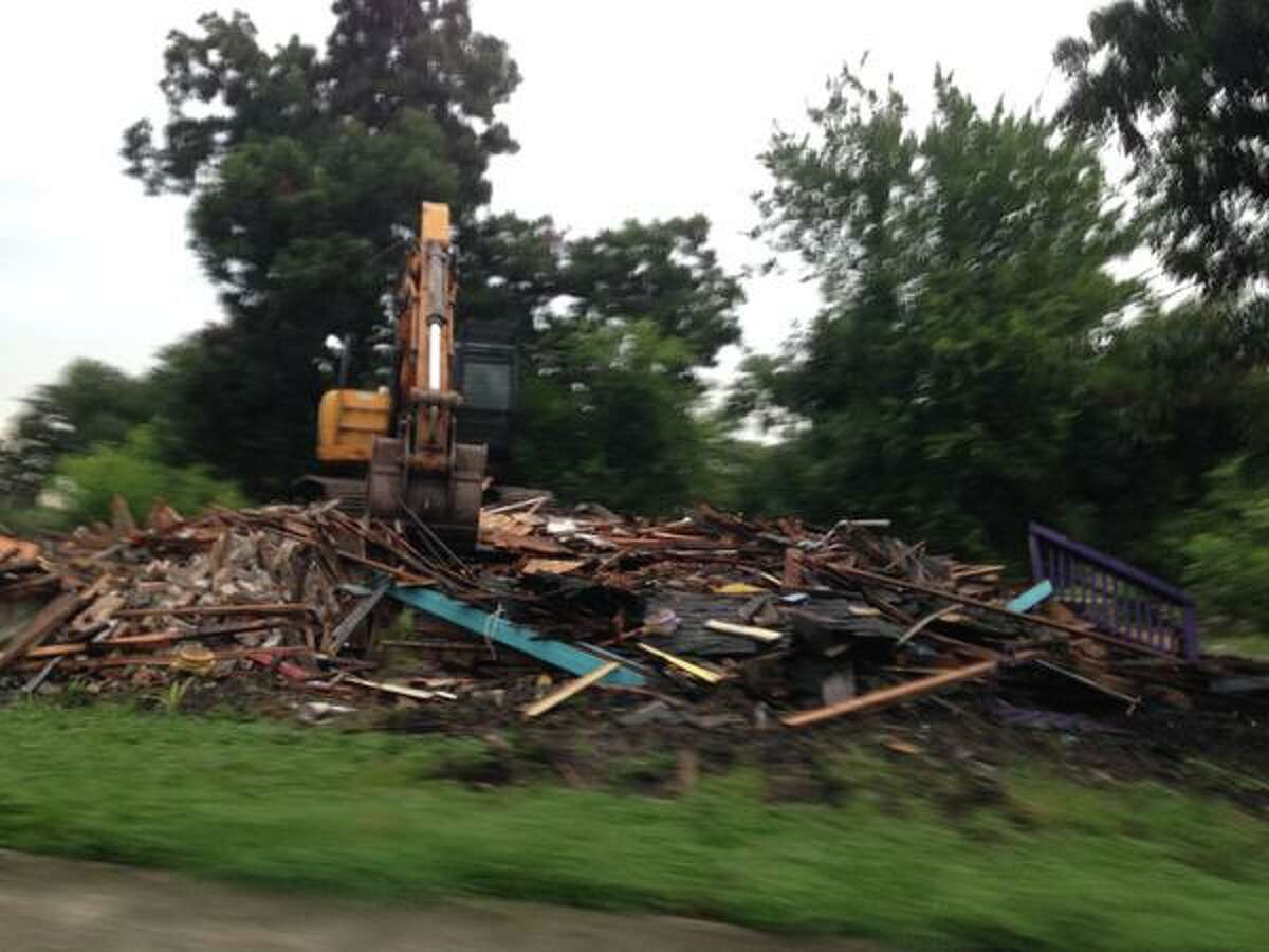 Crews tear down a multi-colored house in Midtown on August 20, 2015. HCC bought the plot where the house stood in 2013 for $12.7 million. The college has no plans for the land.