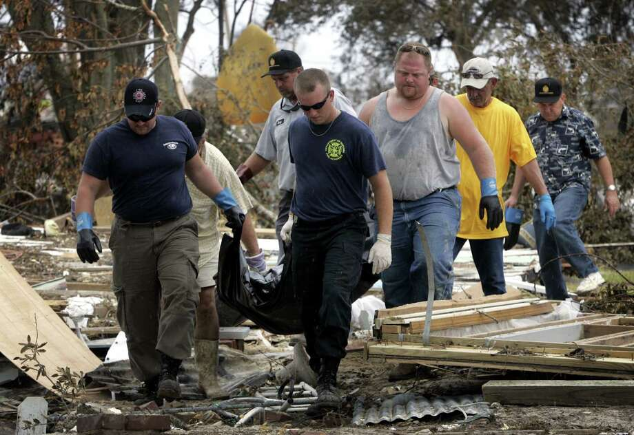Members of the Mississippi Fire Department, funeral employees and volunteers carry the body of a man who was killed when his home collapsed during Hurricane Katrina in Biloxi, Miss. The man was found in the rubble of his home. Photo: BARBARA DAVIDSON, AP / THE DALLAS MORNING NEWS