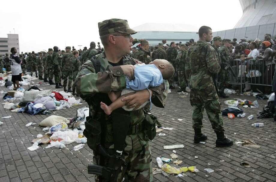 A U.S. soldier tends to a baby as people wait to leave the Superdome in New Orleans.  Rampant lawlessness prompted Louisiana state leaders to ask for up to 40,000 troops to help restore order. Photo: JAMES NIELSEN, AFP/Getty Images / AFP