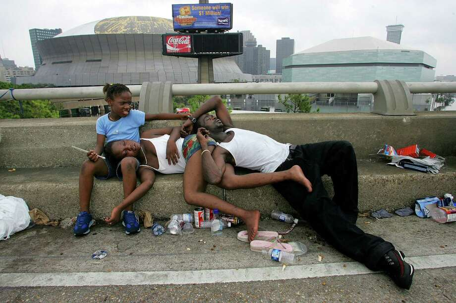 On business 90, the highway running past the Superdome (background), Allrenisha Smith, 10, cradles her mother Camika Smith's head, as Camika and her husband, Ricky Scales, sleep. They decided not to wait at the dome for a ride out. Photo: PAUL MOSELEY, KRT / FORT WORTH STAR-TELEGRAM