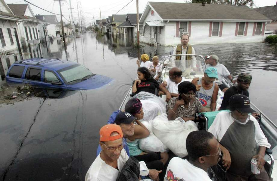 Volunteer Paul Mire, of Destrehan, La., background center, drives his boat out after rescuing residents in New Orleans. Mire was assisting the East Baton Rouge Urban Search and Rescue team in the search for victims of Hurricane Katrina. Photo: IRWIN THOMPSON, AP / DALLAS MORNING NEWS