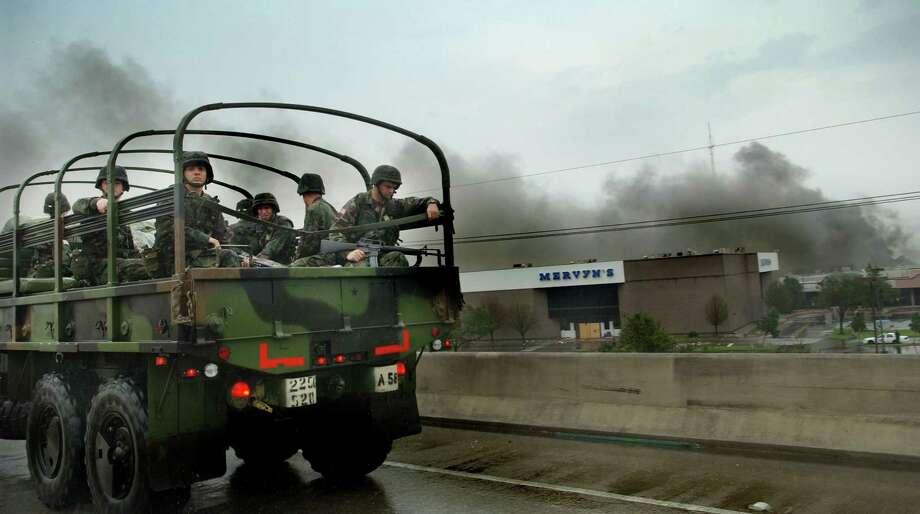 National Guardsmen head into New Orleans as the Oakwood Shopping Center burns nearby. Photo: ROBERTO GONZALEZ, KRT / ORLANDO SENTINEL