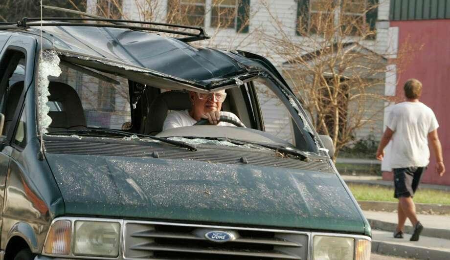 A motorist driving a damaged van negotiates through downtown Biloxi, Miss. Photo: JOE SKIPPER, REUTERS / X00507