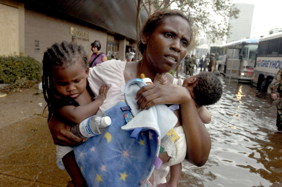 A Hurricane Katrina refugee and her two babies wade through the water out to a waiting chartered bus outside the Hyatt Regency Hotel in New Orleans. Starting with an estimated 16,000-20,000 people and estimated to continue through the night, refugees were walked through the lower level of the hotel to the awaiting air-conditioned buses. Photo: RICHARD ALAN HANNON, AP / THE ADVOCATE