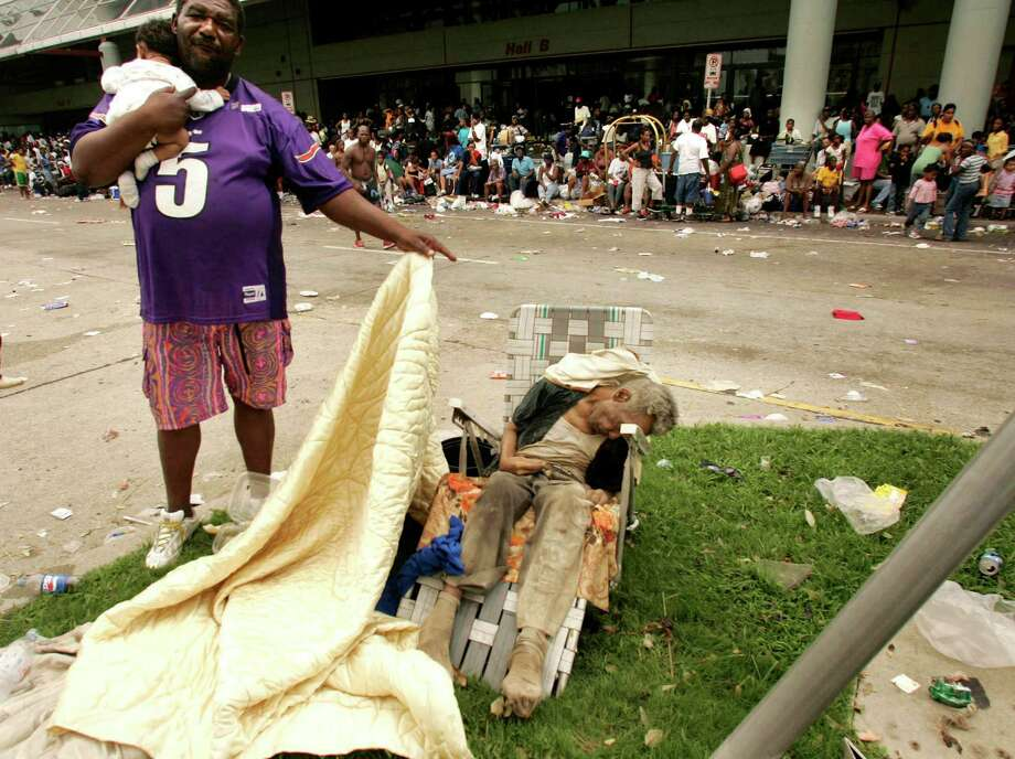A man holding a baby uncovers the body of a dead man, suspected to have been sitting there for two days, outside the convention center in New Orleans. Photo: RICK WILKING, Reuters / X00301