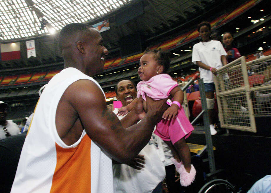 New Orleans Saints' receiver Joe Horn holds Elizabeth Flores, 7 months, from New Orleans  in the Houston Astrodome Saturday, Sept. 3, 2005.  Horn visited the dome to give the displaced residents from New Orleans hope and for thousands of Hurricane Katrina refugees inside the Astrodome, meeting him was a much-needed morale boost. Photo: DWC, AP / AP