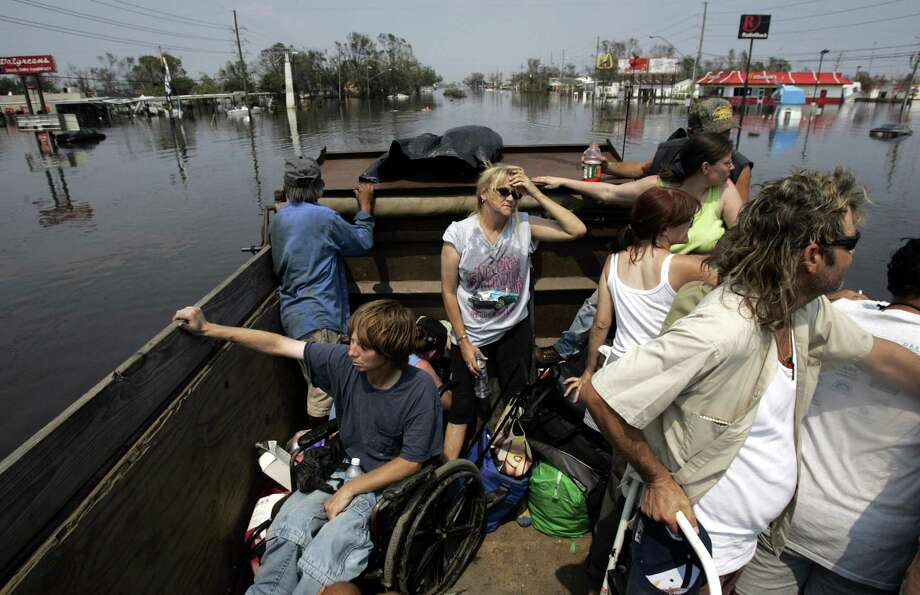 Evacuees are taken out of Chalmette, La., on a dump truck run by locals after Hurricane Katrina hit New Orleans, Saturday September, 03, 2005. Photo: MICHAEL AINSWORTH, KRT / DALLAS MORNING NEWS