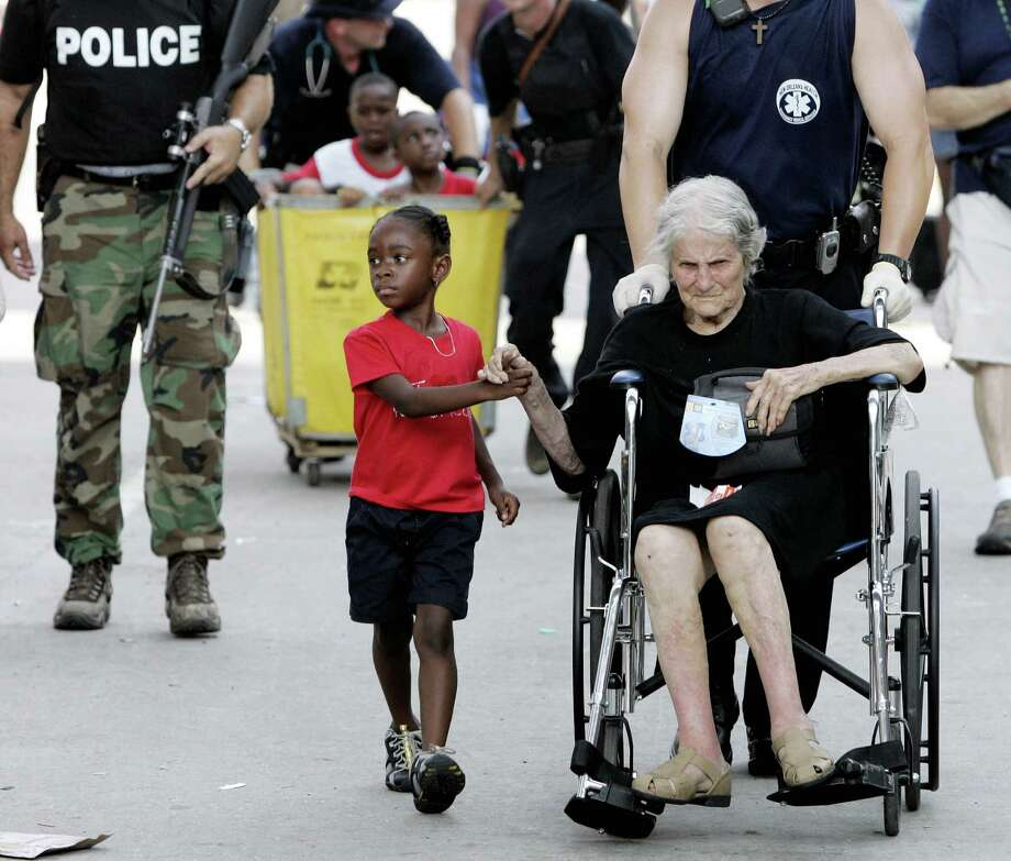 Tanisha Belvin, 5, holds the hand of fellow Hurricane Katrina victim Nita LaGarde, 89, as they are  evacuated from the  Convention Center in New Orleans, La., Saturday, Sept. 3, 2005.  Hunderds of people waited several days to be evacuated. Photo: ERIC GAY, AP / AP