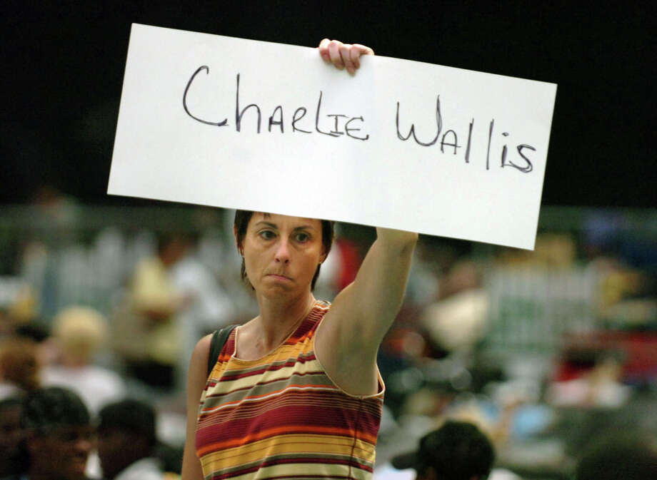 Lisa McClarty of Houston, searches for her uncle, Charlie Wallis of New Orleans, La., inside the Astrodome. McClarty has not seen her uncle in 25 years but learned that he was on a list of survivors sheltered at the Astrodome after Hurricane Katrina. Photo: JIM MACMILLAN, KRT / PHILADELPHIA DAILY NEWS