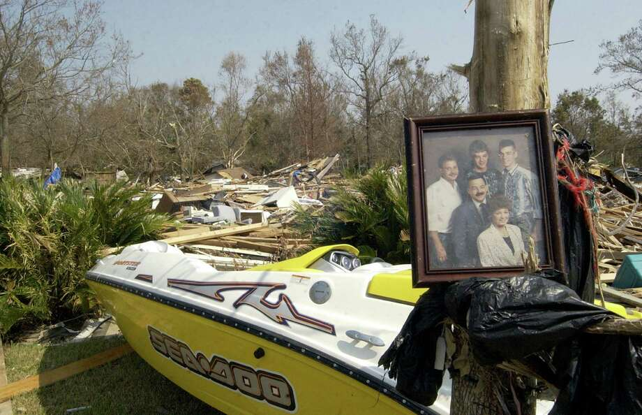A salvaged family portrait hangs on a tree surrounded by piles of debris in Pascagoula, Miss. Photo: CHRISTY PRITCHETT, AP / THE MISSISSIPPI PRESS