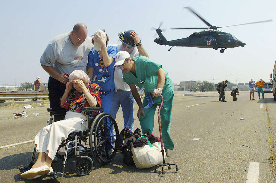Doctors and volunteers cover a lady from flying dust and debris after finding out that there was no more room in a helicopter that was taking evacuees to a shelter Saturday, Sept. 3, 2005, on Interstate 10 in New Orleans. Photo: GABE HERNANDEZ, AP / VALLEY MORNING STAR