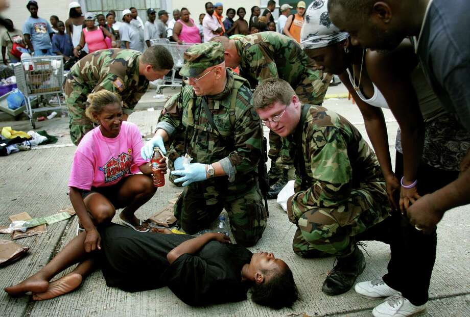 A woman passes out while waiting to be evacuated with scores of people at the Convention Center in downtown New Orleans, La. Photo: KHAMPHA BOUAPHANH, KRT / FORT WORTH STAR-TELEGRAM