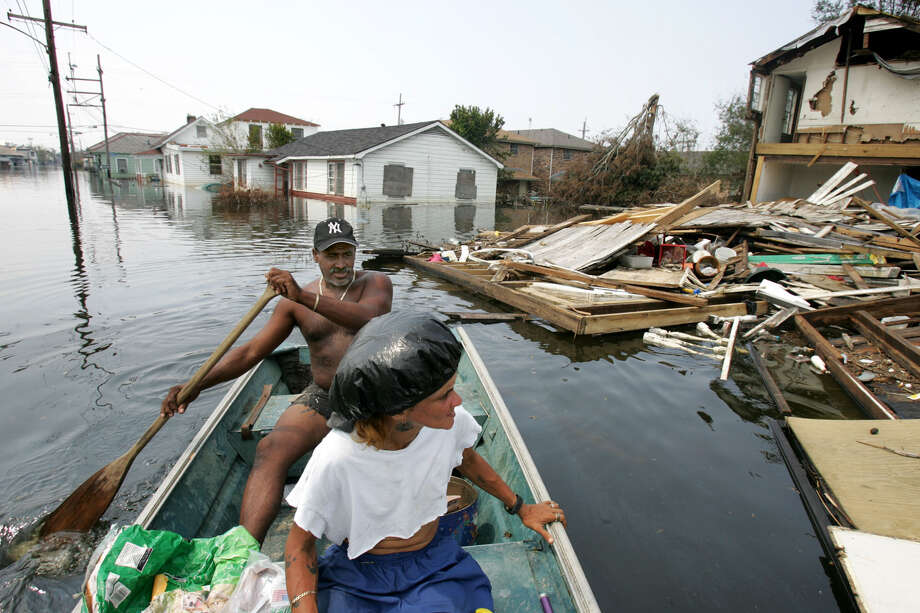 Oakland Pete, behind, and his wife Angela Johnson look at a house destroyed by Hurricane Katrina, Saturday, September 3, 2005. Pete and Angela go around flooded Seventh Ward in New Orleans by boat every day to check on residents who decided to stay in their house. Photo: KUNI TAKAHASHI, KRT / CHICAGO TRIBUNE