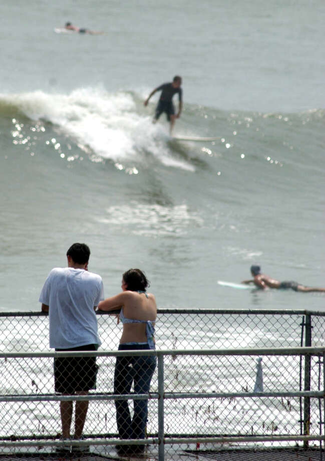 Adrian Mendoza and Lauren Gonzalez, of Houston, watch surfers from the fishing pier at the Flagship Hotel in Galveston Sunday afternoon. Waves along the gulf 