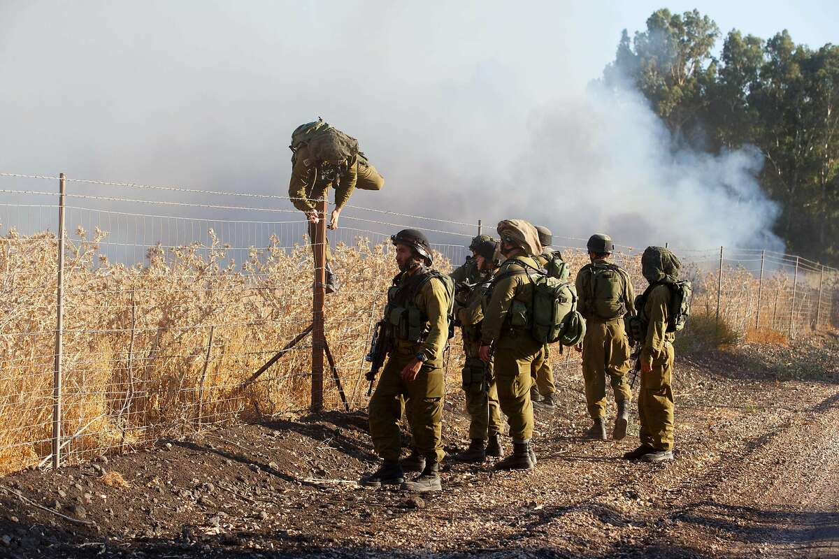 TOPSHOTS Israeli soldiers inspect a field where rockets fired from Syria landed near Kfar Szold, causing fires but no injuries, in northern Israel, close to the Golan Heights and the border with Lebanon, on August 20, 2015. Israel launched artillery and air strikes against Syrian army positions in the Golan Heights overnight in response to rocket fire that hit the Upper Galilee and the Israeli-annexed side of the Golan Heights, according to Israeli military sources. Israel seized 1,200 square kilometres (460 square miles) of the Golan strategic plateau from neighbouring Syria in the 1967 Middle East war. AFP PHOTO / STR == ISRAEL OUT == -/AFP/Getty Images