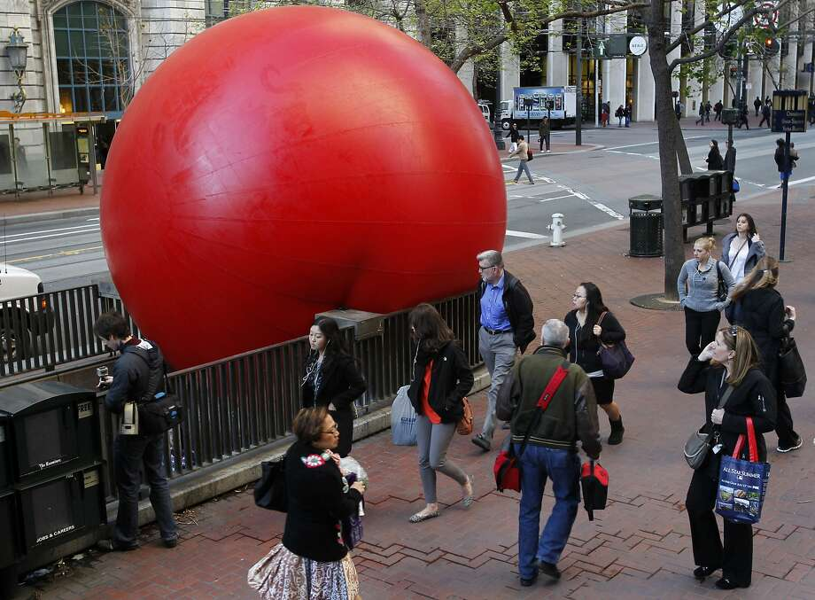 Pedestrians walk past a giant inflatable ball at the Embarcadero BART station in San Francisco, Calif. on Tuesday, April 9, 2013. Artist Kurt Perschke brought his Red Ball Project art installation to the station for the day to entertain and amuse commuters as they arrived and departed. Photo: Paul Chinn, The Chronicle