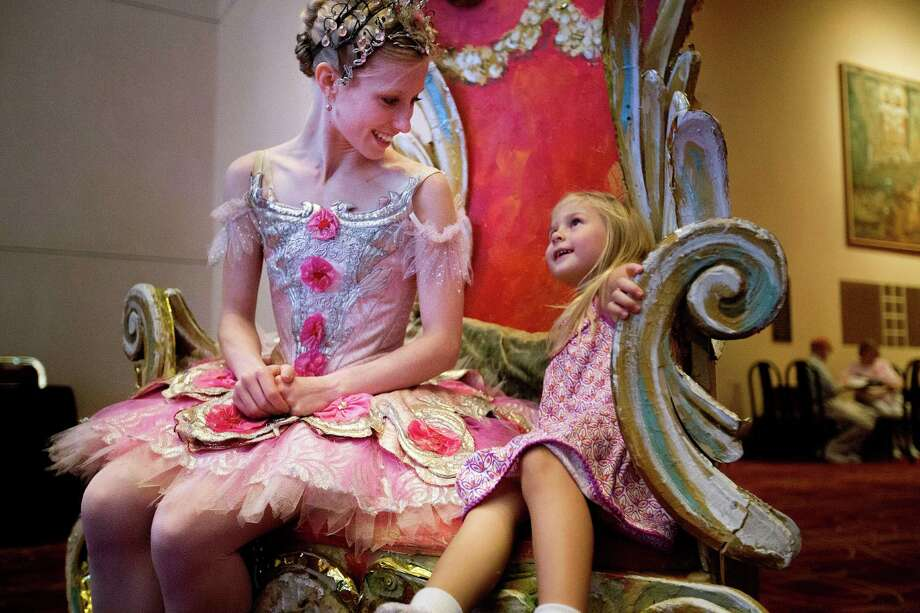 Sophi Lowe, 3, spends time chatting with Houston Ballet's Katelyn May, instead of posing for a picture at the Wortham Theater Center during the 21st Theater District Open House Sunday, Aug. 24, 2014, in Houston. The open house featured, music, dance and theater arts as well as activities for children. The event highlights the performing arts in Houston. ( Johnny Hanson / Houston Chronicle ) Photo: Johnny Hanson, Staff / © 2014  Houston Chronicle