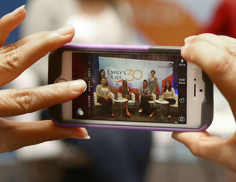 Attendees including Mya Whitaker (middle wearing red) take pictures of themselves on stage after the Ignite Change and young professionals event hosted by Emily's List at St. Regis San Francisco Hotel in San Francisco, Calif., on Friday, August 21, 2015. Photo: Liz Hafalia, The Chronicle