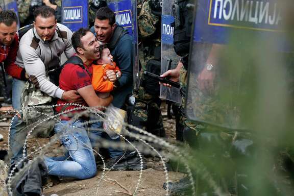 Migrants help a fellow man and young boy who are blocked by Macedonian riot police officers during a clash near the border train station of Idomeni, northern Greece, as they wait to be allowed by the police to cross the border to Macedonia.