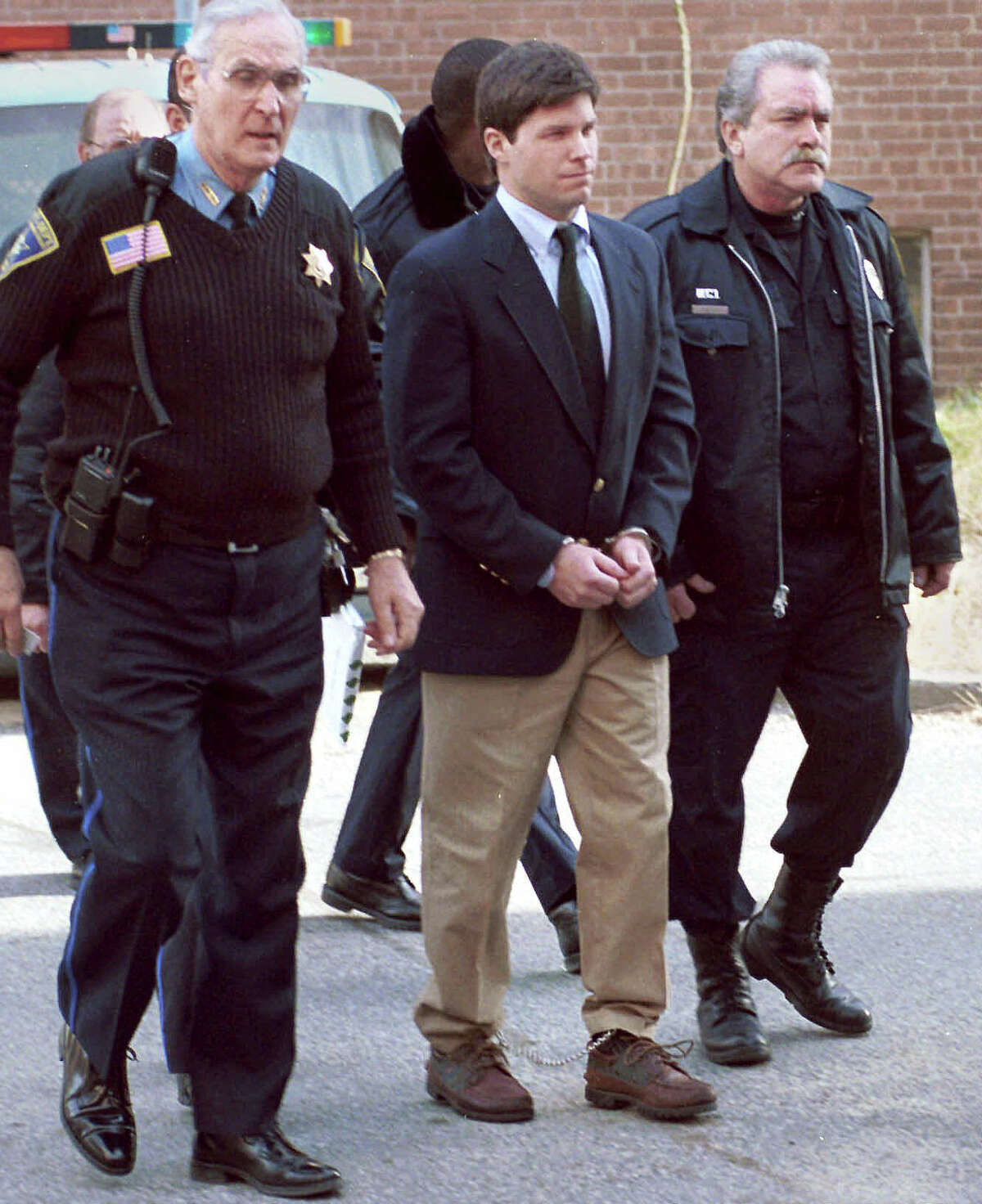 Convicted rapist Alex Kelly, center, is led out of Stamford Superior Court on Dec. 23, 1998. Kelly, who said he was a changed man who is sorry for what he has done during an unsuccesful 2005 bid for parole. But one of his victims says the former international fugitive urged the parole board to keep Kelly behind bars, saying she lived in fear while Kelly enjoyed skiing and mountain climbing in Europe.