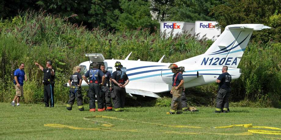 A small jet skid off the runway after landing at  Danbury Municipal Airport Friday afternoon, crashing into a wooded area past the end of the runway. Three people were being treated for minor injuries, according to scanner reports. A man and a woman with neck braces were seen geting into an ambulance. Friday, August 21, 2015, in Danbury, Conn. Photo: H John Voorhees III / Hearst Connecticut Media / The News-Times