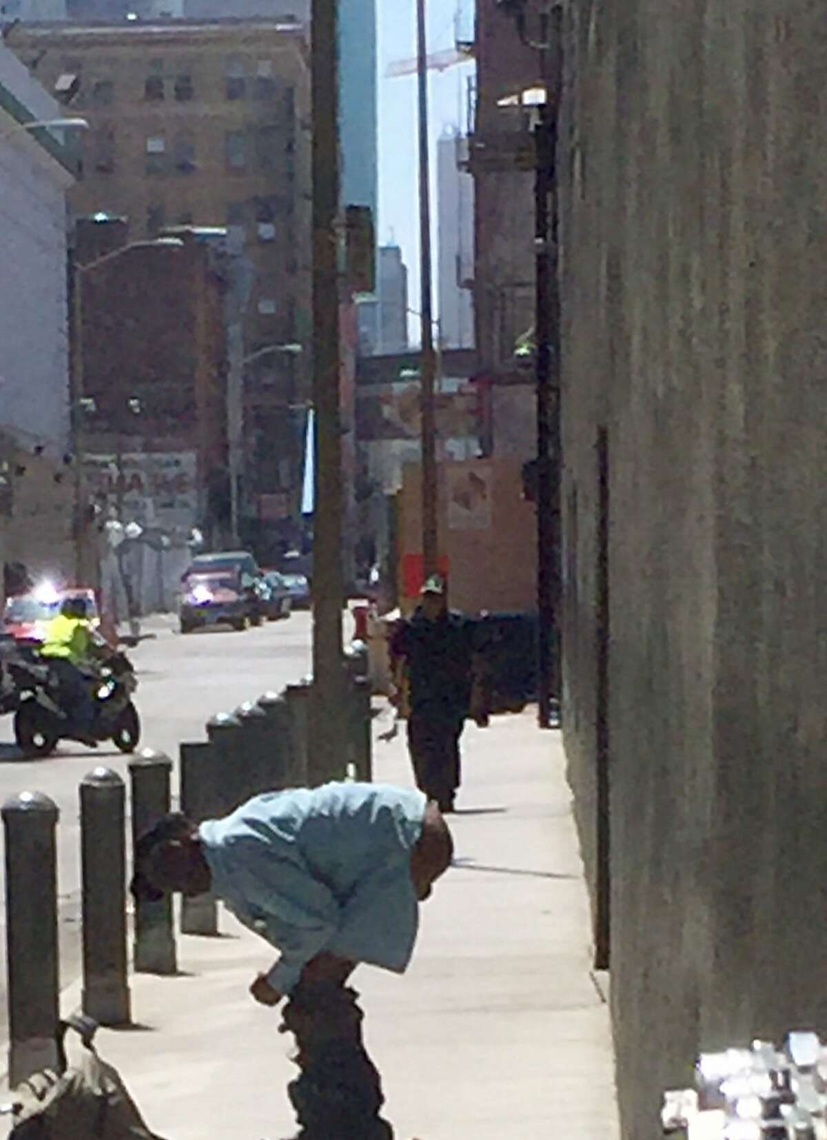 An unidentified man stops to defecate in the Stevenson St. alley behind Nordstrom Rack at 5th and Market Streets on Aug. 17.
