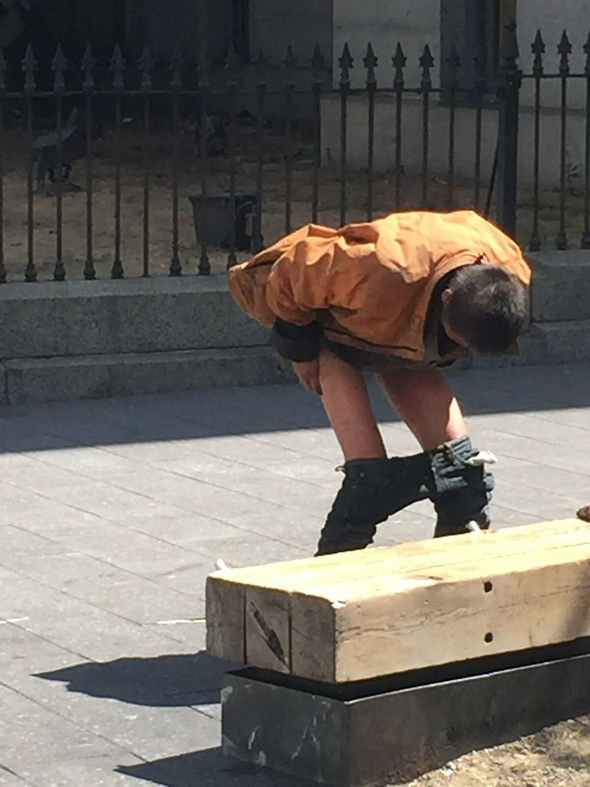 A homeless man squats to defecate at Mint Plaza, just off 5th Street, on Aug. 17