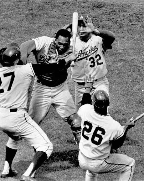 Giants pitcher Juan Marichal (27) swings a bat at Dodgers catcher John Roseboro (8) as Dodgers pitcher Sandy Koufax (32) jumps in to stop the fight during a game at Candlestick Park in San Francisco on Aug. 22, 1965. Marichal was apparently angered when Roseboro threw a pitch too close to Marichal's head. Photo: Charles Doherty, AP