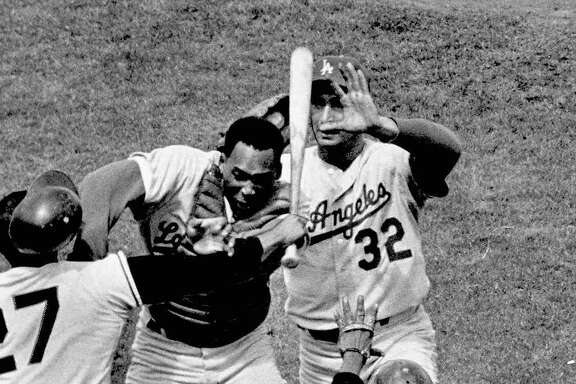 ** FILE ** San Francisco Giants pitcher Juan Marichal (27) swings a bat at Los Angeles Dodgers catcher John Roseboro (8) as Dodgers pitcher Sandy Koufax (32) jumps in to stop the fight during a game at Candlestick Park in San Francisco on Aug. 22, 1965.  Marichal was apparently angered when Roseboro threw a pitch too close to Marichal's head.  Roseboro died after a lengthy illness, a family spokeswoman said Monday, Aug. 19, 2002. He was 69.  (AP Photo/San Francisco Examiner, Charles Doherty)