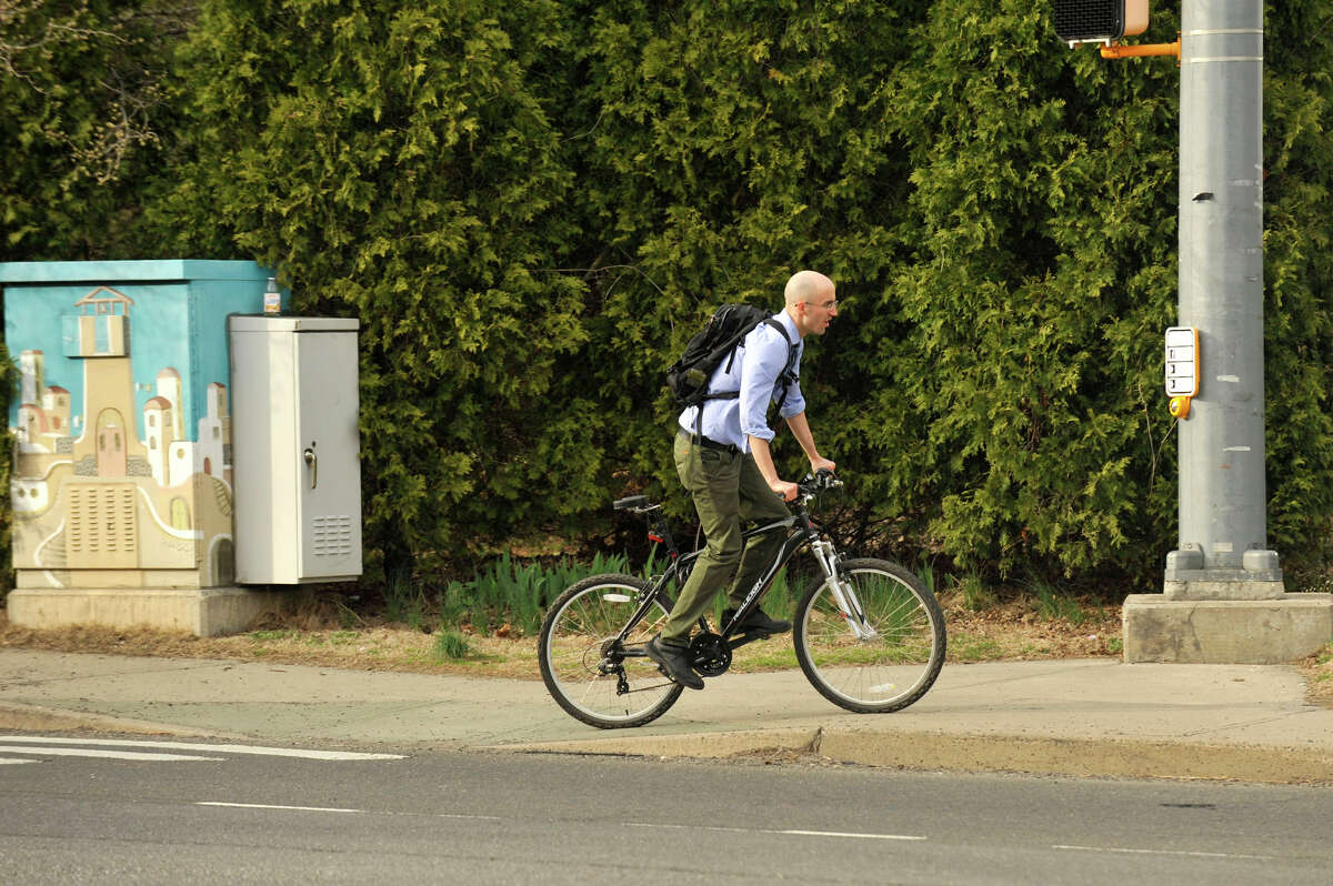 A bicyclist finishes crossing Washington Boulevard in Stamford. The city is considering adding designated bike lanes to increase safety.
