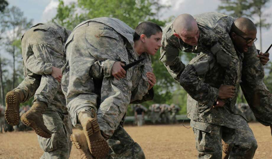 Capt. Kristen Griest, center, one of two women becoming the first female soldiers to graduate from Army Ranger School, carries another soldier while holding a knife.  Photo: THE WASHINGTON POST, STR / Washington Post / Staff Sgt. Scott Brooks/U.S. Army