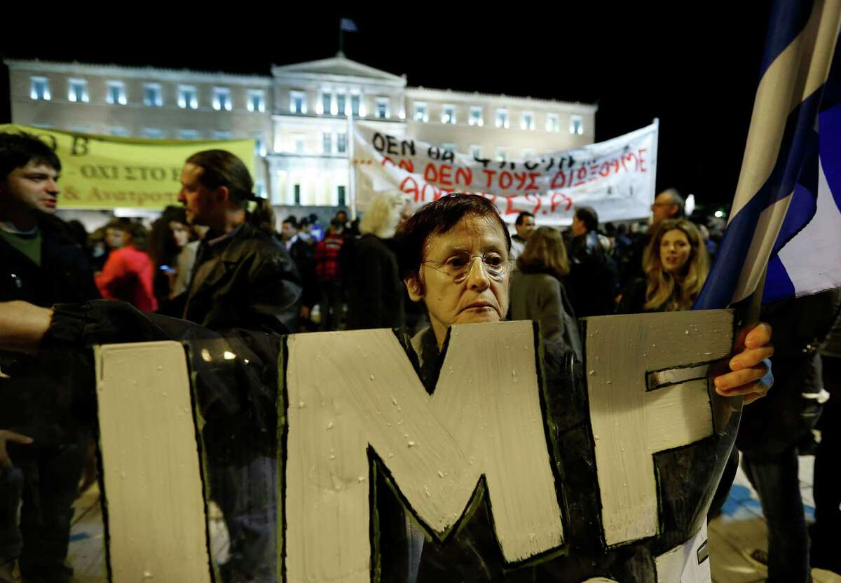 A woman holds an IMF banner in front of the Parliament in Athens on Sunday Nov. 11, 2012. Hundreds of protesters were converging on the Greek capital's main square outside Parliament on Sunday evening, as lawmakers debated the 2013 budget, which includes pension and salary cuts demanded by the country's international creditors in order for them to approve the next vital batch of rescue loans. Lawmakers were to vote at midnight or shortly after, and the legislation is expected to pass. The vote comes four days after a separate bill of deep spending cuts and tax hikes for 2013-14 squeaked past with a narrow majority in the 300-member Parliament following deep disagreements among the members of Greece's three-party coalition government.(AP Photo/Lefteris Pitarakis)