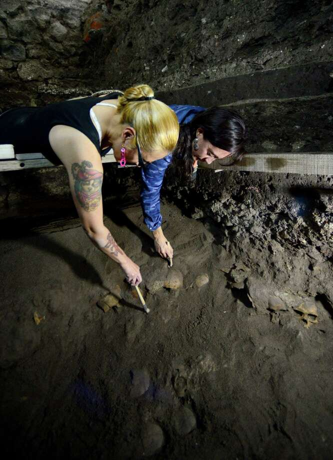 Archaeologists suspended above the Mexico City excavation site use brushes to carefully remove soil from the rack of skulls. Photo: Hector Montano /Mexico National Anthropology And History Institute /AFP / Hector Montano