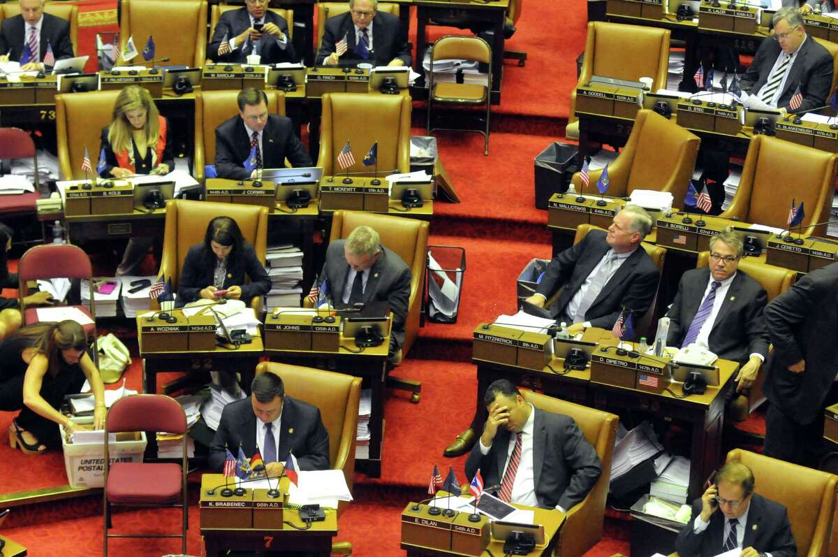 New York State Assembly members pass bills during session at the Capitol on Thursday June 18, 2015 in Albany, N.Y. (Michael P. Farrell/Times Union)