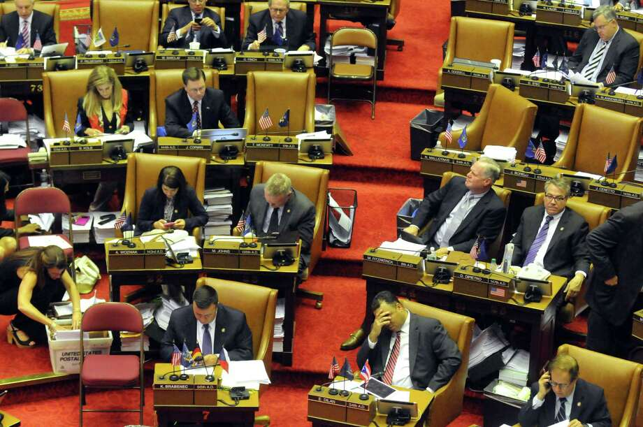New York State Assembly members pass bills during session at the Capitol on Thursday June 18, 2015 in Albany, N.Y.  (Michael P. Farrell/Times Union) Photo: Michael P. Farrell / 00032332A