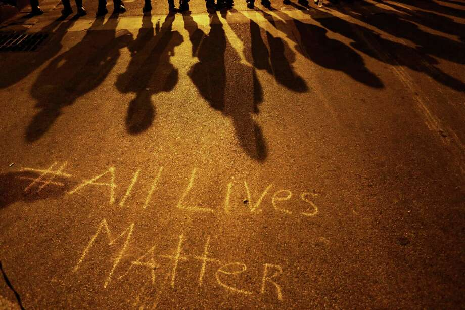 "A message reading ""All Lives Matter"" is written on the pavement as police in riot gear cast shadows while standing in line ahead of a curfew Friday, May 1, 2015, in Baltimore. (AP Photo/David Goldman) Photo: David Goldman, STF / AP"