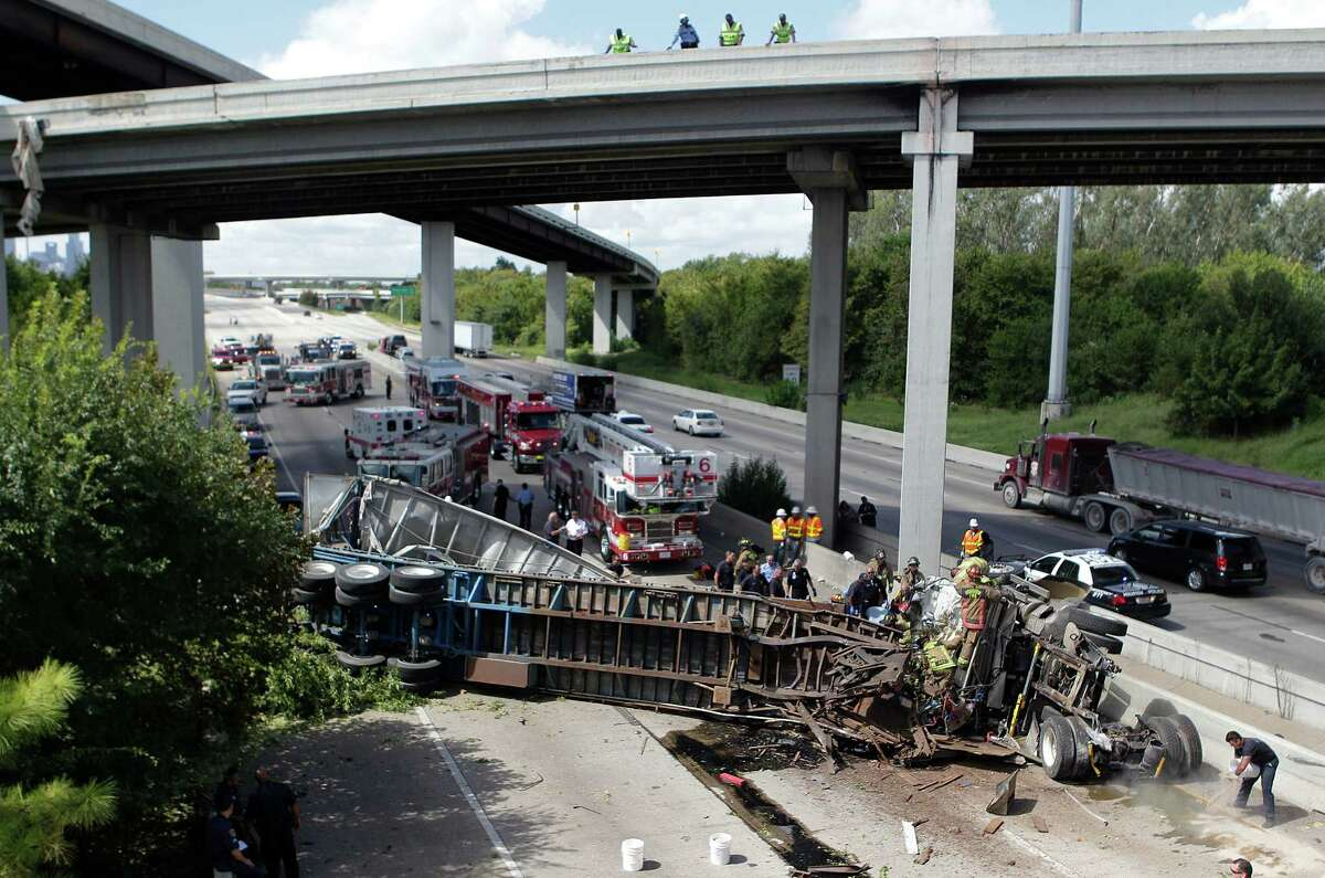 HPD and HFD responded to an accident where the driver of a big-rig was traveling outbound Eastex Freeway to North Loop ramp fell off the overpass and landed on Eastex Freeway northbound on Wednesday, Sept. 10, 2014, in Houston. The truck dangled briefly from the ramp before falling 46 feet to the freeway below. No other vehicles were hit. The driver was injured but was able to talk to the responders extricating him from the cab. The driver was taken to an area hospital and is expected to survive. ( Mayra Beltran / Houston Chronicle )