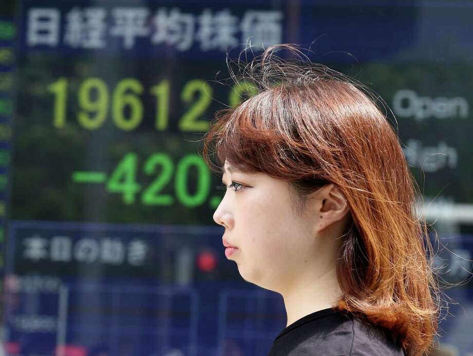 A woman walks past an electronic stock board of a securities firm in Tokyo, Friday, Aug. 21, 2015. Tokyo's Nikkei 225 plunged 2 percent in the morning session as Asian stocks fell further Friday after a survey showed Chinese manufacturing weakened this month. (AP Photo/Koji Sasahara) ORG XMIT: KSX103 Photo: Koji Sasahara / AP