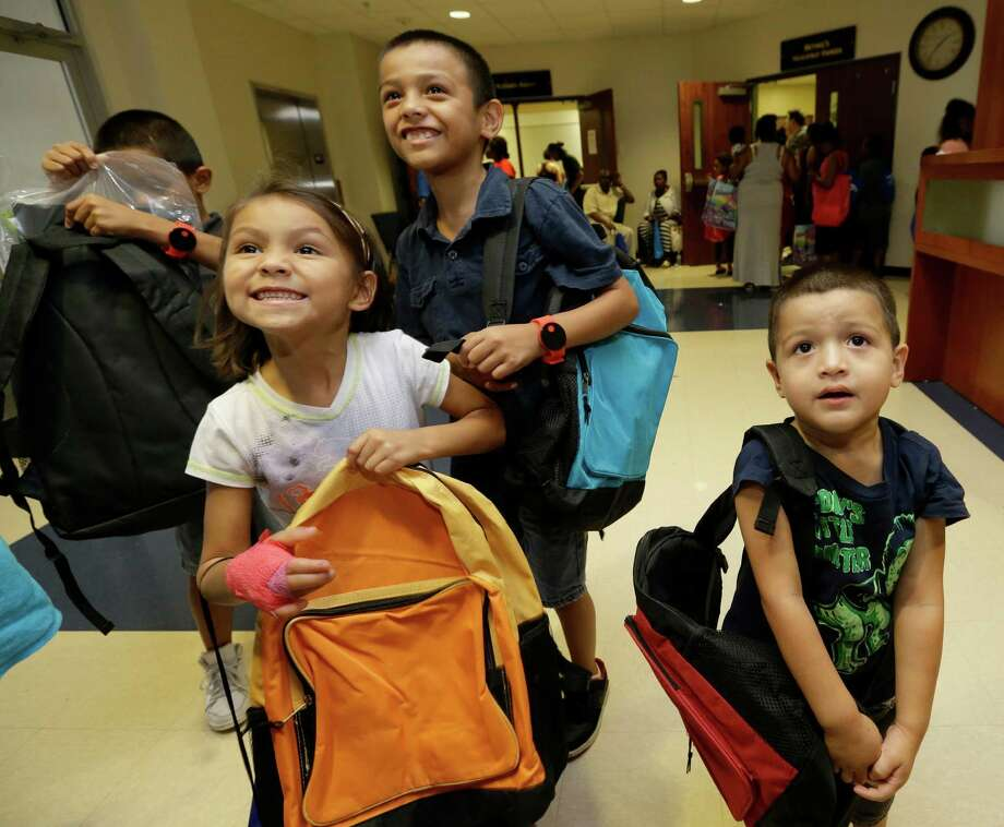 Siblings Rigoberto Romeo, 10, left,  Aaliyah Romeo, 6,  Angela Romeo, 9, and Hugo Romeo, 4, right, recieve backbacks during the fourth annual Back-to-School Extravaganza at Bethel's Place Empowerment Center, 12660 Sandpiper Dr., Friday, Aug. 21, 2015, in Houston.   ( Melissa Phillip  / Houston Chronicle ) Photo: Melissa Phillip, Staff / © 2015 Houston Chronicle