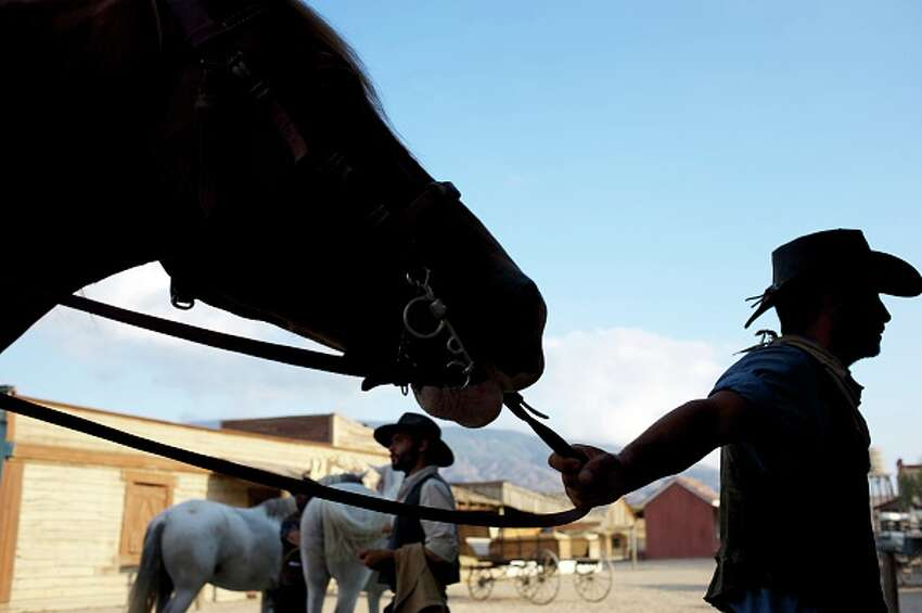 ALMERIA, SPAIN - AUGUST 20: Stunt actors keep horses after a show for tourists at Fort Bravo/Texas Hollywood on August 20, 2015 in Almeria, Spain. Fort Bravo Texas Hollywood, built in the 1960s in Almeria, Spain, is a western style set for films, which is also used for tourist tours. Originally used by film director Sergio Leone for 'A Fistful of Dollars', 'For a Few Price' and 'The Good, the Bad and the Ugly', which lead to the Spaghetti Western genre, today it is still used to shoot many different types of films. (Photo by Juan Naharro Gimenez/Getty Images)