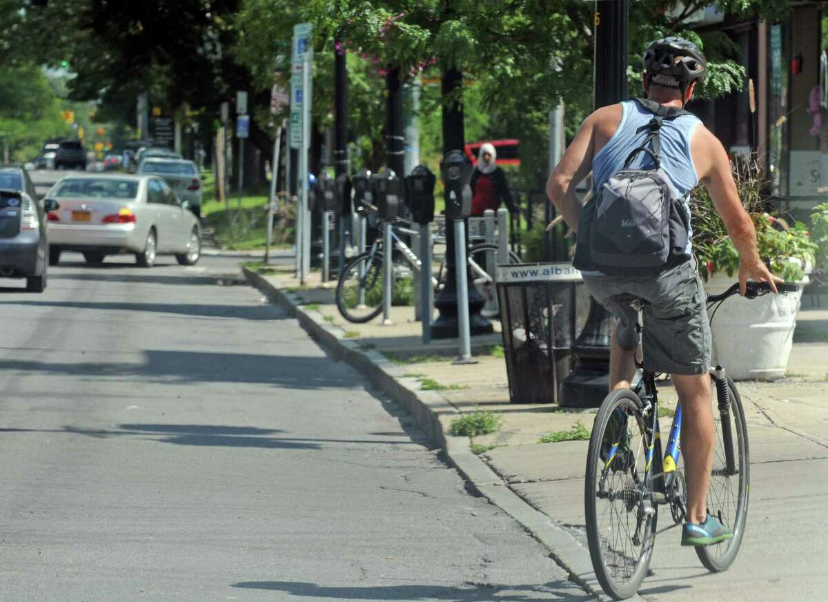 A man bicycles down Madison Avenue on Friday Aug. 21, 2015 in Albany, N.Y. (Michael P. Farrell/Times Union)