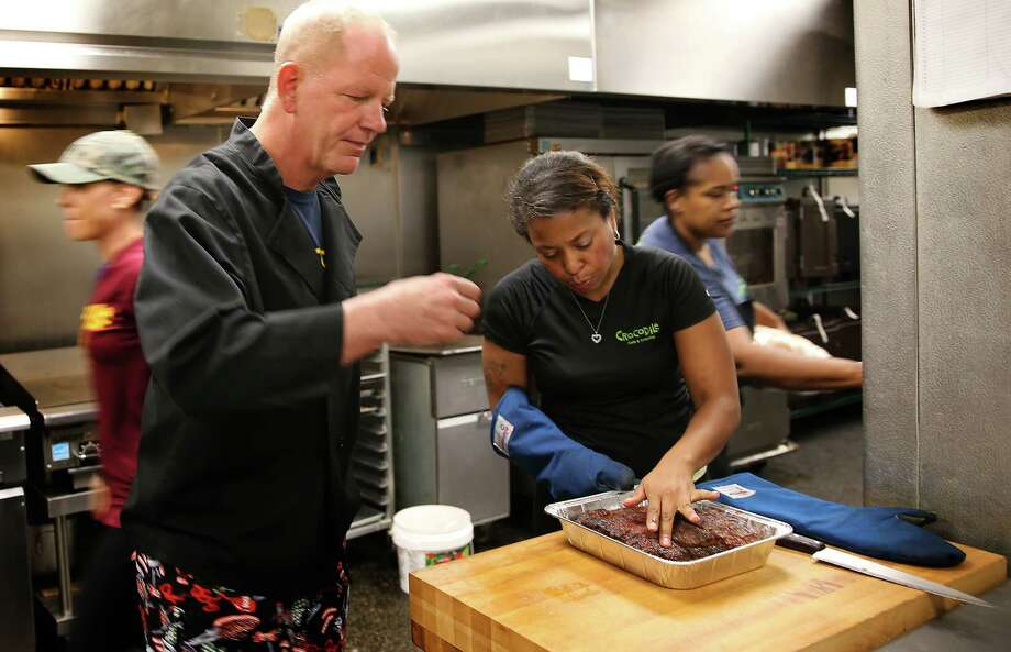 Kurt Linneman, left, executive chef and owner of Crocodile Cafe & Catering, tests a piece of brisket as Koren Griffen, right, looks it over in the company's kitchen on July 14, 2015 in Wayne, Pa. (David Maialetti/Philadelphia Inquirer/TNS) Photo: David Maialetti, MBR / Philadelphia Inquirer