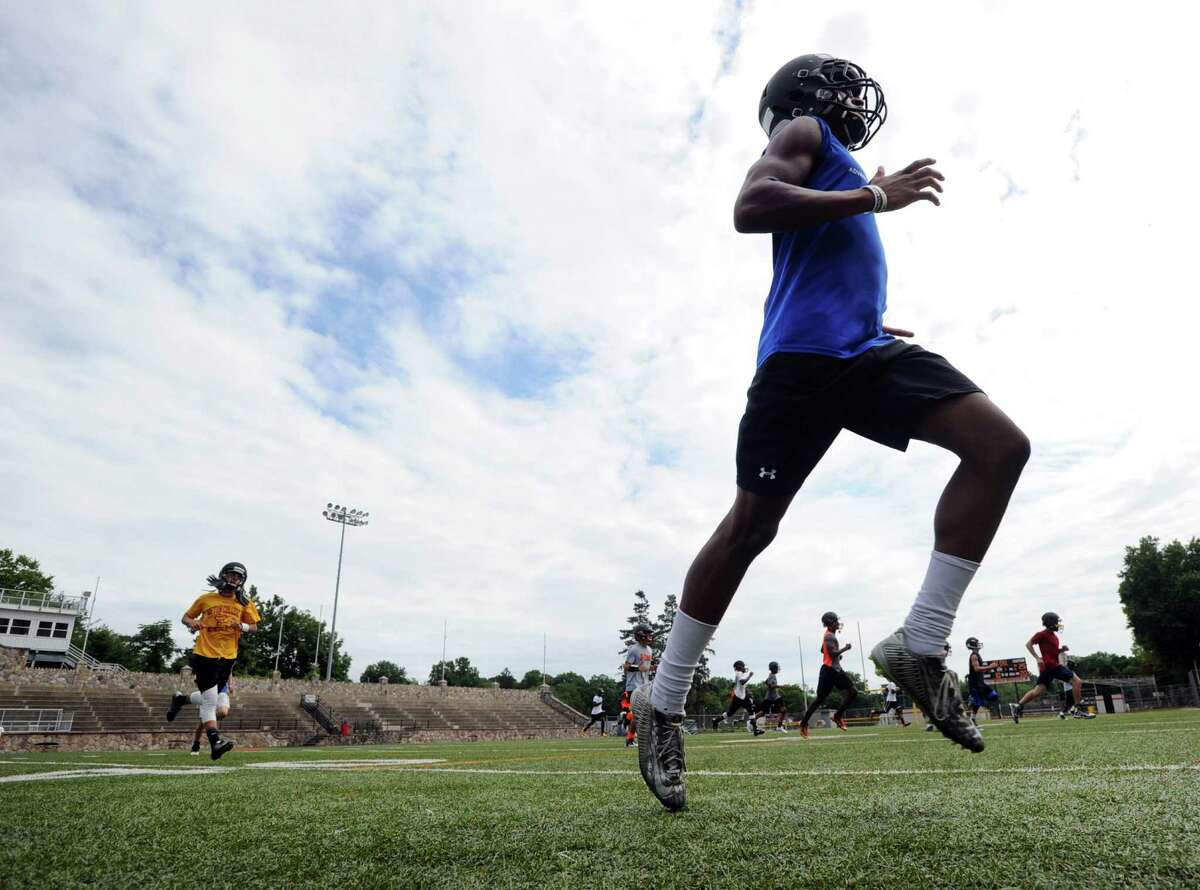 At right, Stamford High School football player, Omar Fortt, runs wind-sprints during the first day of football practice at the school in Stamford, Conn., Friday, Aug. 21, 2015.