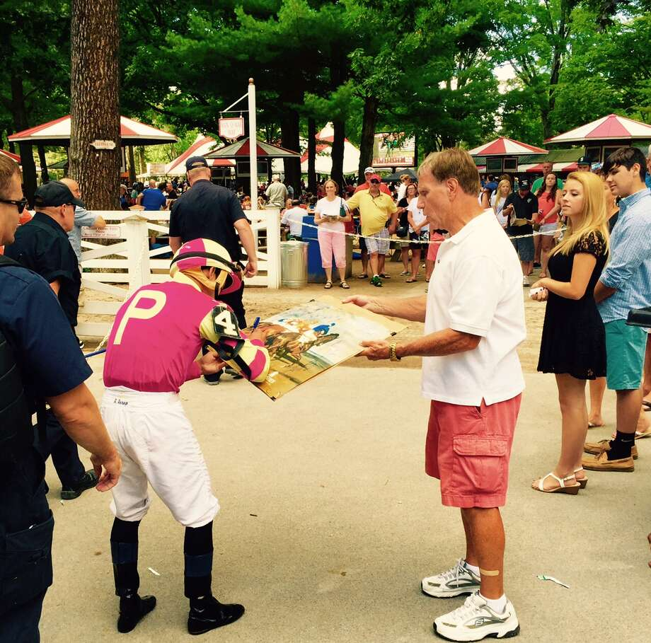 Want a jockey's autograph? Catch up with the riders as they depart the jockey's room on the way to the paddock before each race. Like right here. Jockey Angel Arroyo pauses to sign his name for a fan before the fourth race at the Spa on Friday. Hope Arroyo wasn't giving any touts on his mount, Lady in Shades, to the guy he signed for. Lady in Shades finished fourth in the race, which was run on the main track after being taken off the grass. —Tim Wilkin