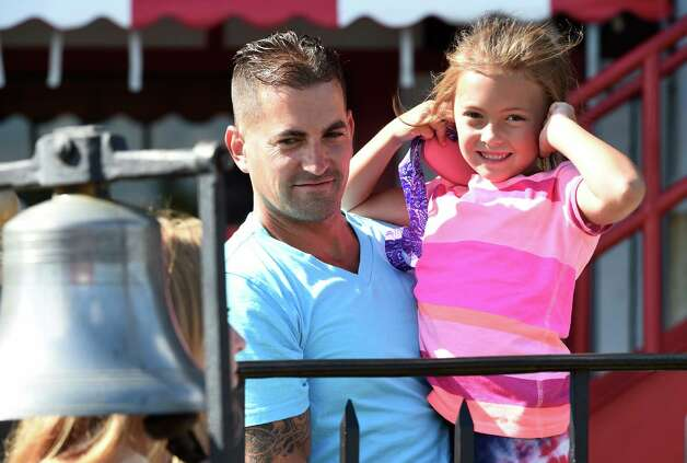 Taylor Boldt 7, in the arms of her father Josh Boldt, holds her ears as the traditional bell tolls at the Saratoga Race Course Friday afternoon Aug. 21, 2015 in Saratoga Springs, N.Y.    (Skip Dickstein/Times Union) Photo: SKIP DICKSTEIN