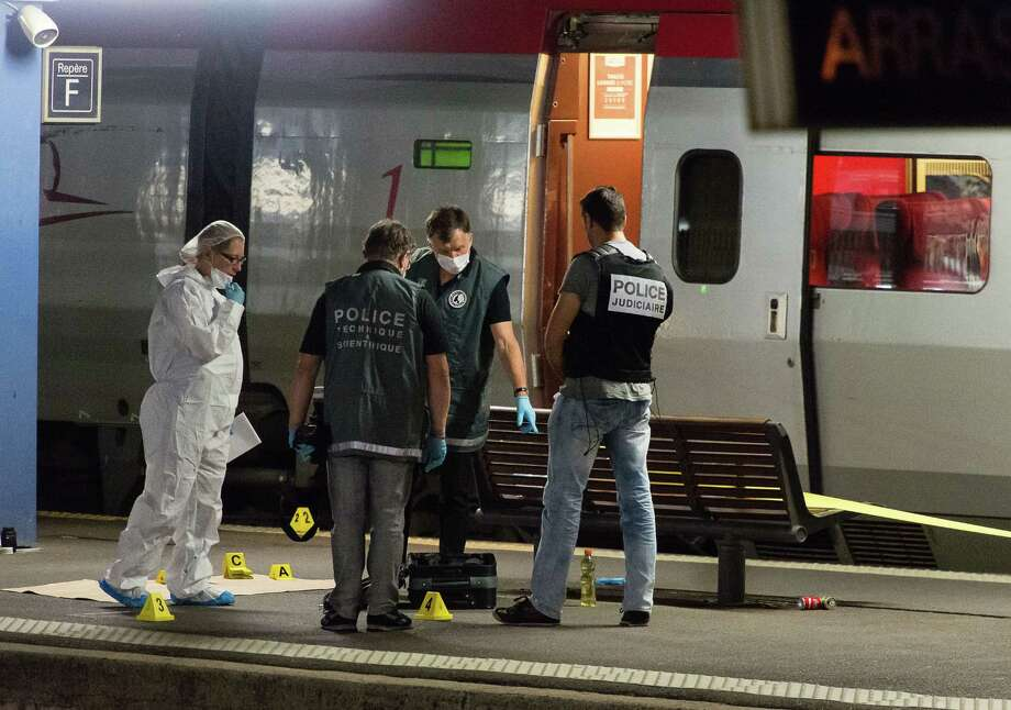 Police officers work on a platform next to a Thalys train at Arras train station, northern France, Friday, Aug. 21, 2015. A gunman opened fire with an automatic weapon on a high-speed train traveling from Amsterdam to Paris Friday, wounding three people before being subdued by two American passengers, officials said. French Interior Minister Bernard Cazeneuve, speaking in Arras in northern France where the suspected was detained, said one of the Americans was hospitalized with serious wounds. (AP Photo) ORG XMIT: REB104 / AP